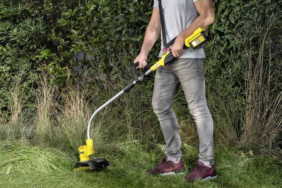 Резка травы в саду аккумуляторным триммером